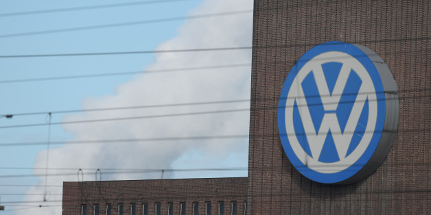 A man looks through binoculars as he stands next to a corporate logo of Volkswagen on the rooftop of the former power plant of the German car manufacturer inWolfsburg, Germany, Friday, Sept. 25, 2015. Volkswagen's supervisory board is meeting Friday to discuss who to name as CEO after Martin Winterkorn quit the job this week over an emissions-rigging scandal that's rocking the world's top-selling automaker. (Rainer Jensen/dpa via AP)
