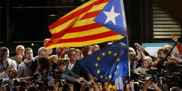 "A ""estelada"" or pro independence flag and a European Union flag are waved in front of the President of Democratic Convergence of Catalonia Artur Mas, center in front of supporters in Barcelona, Spain, Sunday Sept. 27, 2015. Voters in Catalonia participated in an election Sunday that could propel the northeastern region toward independence from the rest of Spain or quell secessionism for years. An exit poll predicts that pro-independence parties in Spain's Catalonia region are likely to win a maj"