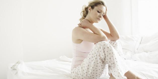 Portrait d'une femme fatiguée assise dans le lit