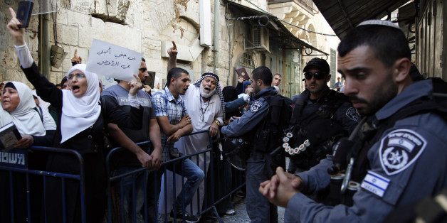 Israeli border police officers stand guard as Palestinians protest in the Old City of Jerusalem on Thursday, Sept. 17, 2015. A rectangular hilltop compound in Jerusalem is ground zero of the Israeli-Palestinian conflict. Known to Muslims as the Noble Sanctuary, it is Islam's third holiest spot. But to Jews it is the Temple Mount, their holiest place. This sensitive arrangement, and attempts to change it, lie at the heart of the unrest that rocked Jerusalem this week. (AP Photo/Mahmoud Illean)