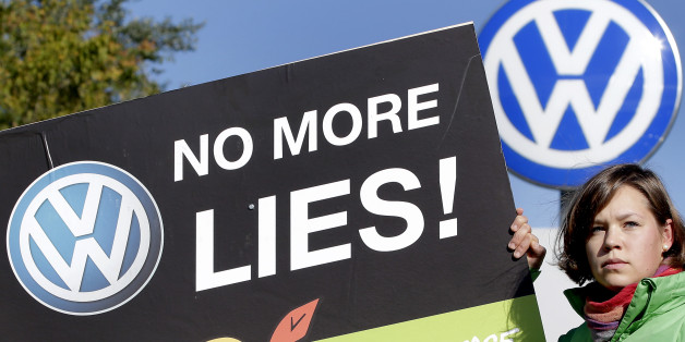 An activist of the environmental protection organization 'Greenpeace' holds a protest poster in front of a factory gate of the German car manufacturer Volkswagen in Wolfsburg, Germany, Friday, Sept. 25, 2015. (AP Photo/Michael Sohn)