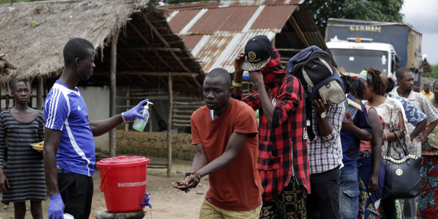 In this photo taken Wednesday, Aug. 12, 2015, a man takes checks people's temperature and helps to wash their hands as they leave Ebola quarantine, after Sierra Leone President Ernest Bai Koroma cut a tape to release the quarantine in the village of Massessehbeh on the outskirts of Freetown, Sierra Leone.  Five months after a man traveled to his home village for festivities marking the end of Ramadan, and died suddenly from Ebola, but now President Koroma came to cut down the fencing to mark the formal end of Sierra Leone's largest remaining Ebola quarantine. (AP Photo/Sunday Alamba)