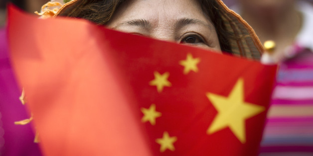 A Chinese woman holds a national flag as Chinese people gather at Jingshan Park to sing patriotic songs to celebrate the up-coming 90th anniversary of the founding of the Communist Party of China in Beijing, China Tuesday, June 14, 2011. China will celebrate the anniversary on July 1. (AP Photo/Andy Wong)