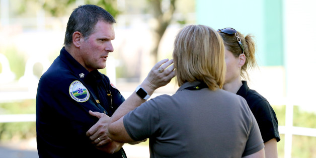 An Oregon Emergency Medical Technician, left, speaks with others at the county fairgrounds in Roseburg, Ore., Thursday, Oct. 1, 2015, following a deadly shooting at nearby Umpqua Community College. Students and faculty were bused to the fairgrounds where counselors were available and some parents waited for their children. (AP Photo/Ryan Kang)