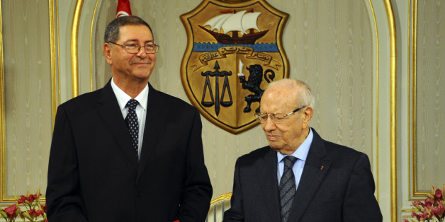 Habib Essid, 65, left, takes a document from newly elected Tunisian President Beji Caid Essebsi as he is asked to form a coalition and name a Cabinet over the next month, Monday, Jan.5, 2015 in Tunis. Tunisia's largest political party chose a veteran from the country's former dictatorship as its candidate for prime minister Monday and he began work immediately on forming a coalition government. (AP Photo/Hassene Dridi)