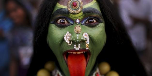 An Indian man dressed as Hindu Goddess Kali participates in a religious procession to mark 'Ram Navami' festival in New Delhi, India, Friday, April 19, 2013. Ram Navami celebrates the birthday of Hindu god Rama. ( (AP Photo/Kevin Frayer)
