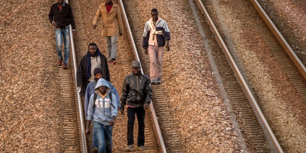 Migrants walk on railway tracks in Coquelles, near Calais northern France, headed toward the Eurotunnel terminal on August 12, 2015. Some 3,000 migrants and refugees, including many fleeing war and persecution in countries like Syria, Libya and Eritrea, are camped out in a makeshift tent village in Calais waiting for a chance to cross to Britain. AFP PHOTO / PHILIPPE HUGUEN        (Photo credit should read PHILIPPE HUGUEN/AFP/Getty Images)