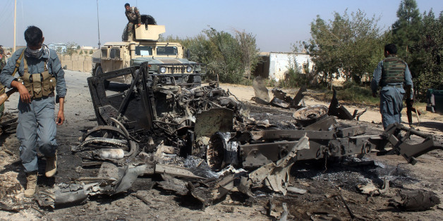 """Afghan security forces inspect the site of a U.S. airstrike in Kunduz city, north of Kabul, Afghanistan, Friday, Oct. 2, 2015. The new leader of the Afghan Taliban says their capture of the northern city of Kunduz was a """"symbolic victory"""" that showed the strength of the insurgency — even though the Taliban pulled out of the city after three days. (AP Photo)"""
