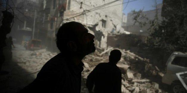 Des Syriens regardent les dégâts provoqués par des frappes aériennes sur la zone rebelle de Douma, à l'est de Damas, le 2 octobre 2015
