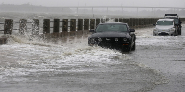 Waves break over a wall around cars parked on Bay Street in Charleston, S.C., Saturday, Oct. 3, 2015.  A flash flood warning was in effect in parts of South Carolina, where authorities shut down the Charleston peninsula to motorists.  (AP Photo/Chuck Burton)