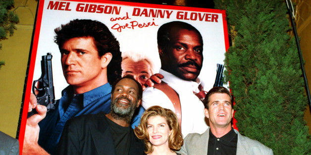 "Co-stars Danny Glover, left, Rene Russo, center, and Mel Gibson pose in front of a ""Lethal Weapon 3"" poster at the movie's premiere at the Mann Village Theater in Westwood, Ca., Monday, May 11, 1992.  (AP Photo/Reed Saxon)"