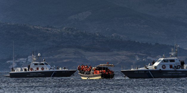 A boat carrying refugees and migrants stops between two Hellenic coast guard boats near the Greek island of Lesbos on September 30, 2015. Europe's migrant crisis was set to be in focus at the UN with Secretary General Ban Ki-moon seeking to muster a global response to the exodus of vast numbers of people from Syria and elsewhere. AFP PHOTO / ARIS MESSINIS        (Photo credit should read ARIS MESSINIS/AFP/Getty Images)