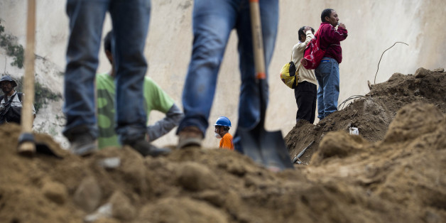 Neighbors, right,  look on as they wait for news as rescue workers continue the search at the site of a landslide in Cambray, a neighborhood in the suburb of Santa Catarina Pinula, about 10 miles east of Guatemala City, Saturday, Oct. 3, 2015. The hill that towers over Cambray collapsed late Thursday after heavy rains, burying several houses with dirt, mud and rocks.  The death toll rose to 30 amid fears that hundreds more could still be buried in the rubble. (AP Photo/Moises Castillo)