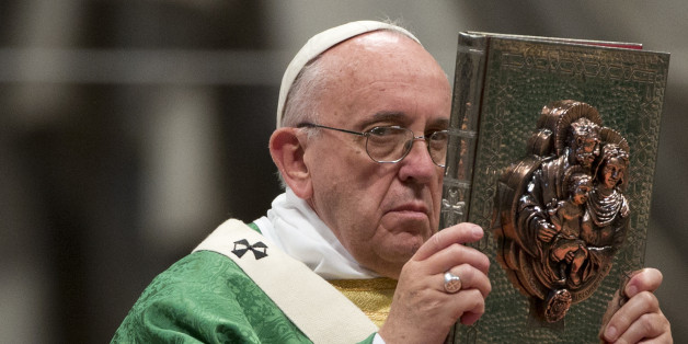 Pope Francis raises the book of the Gospels as he celebrates the opening Mass of the Synod of bishops, in St. Peter's Basilica at the Vatican, Sunday, Oct. 4, 2015. (AP Photo/Alessandra Tarantino)