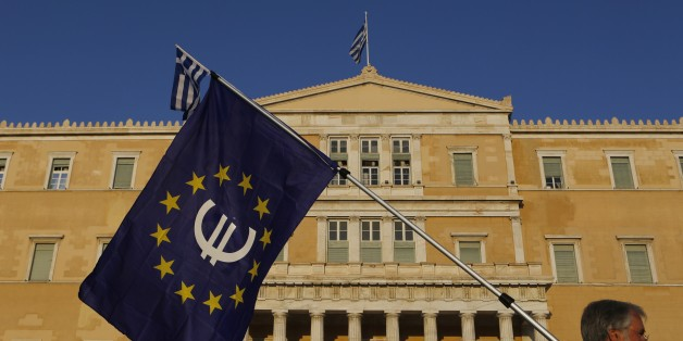 A pro-Euro demonstrator holds a European Union flag in front of Greek Parliament during a rally at Syntagma square in Athens, Thursday, July 9, 2015. Hopes that Greece can get a rescue deal that will prevent a catastrophic exit from the euro rose on Thursday, after key creditors said they were open to discussing how to ease the country's debt load, a long-time sticking point in their talks. (AP Photo/Petros Karadjias)