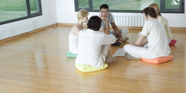 Group therapy session, adults sitting in circle on floor, talking