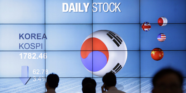 People walk past in front of the screen showing Korea Composite Stock Price Index (Kospi) in Seoul, South Korea, Friday, May 18, 2012. South Korea's Kospi lost 3.4 percent or 62.78 points at 1,782.46.  Asian stocks dived Friday after discouraging U.S. economic reports unnerved investors already worried about the stability of the 17-country euro currency union. (AP Photo/Lee Jin-man)
