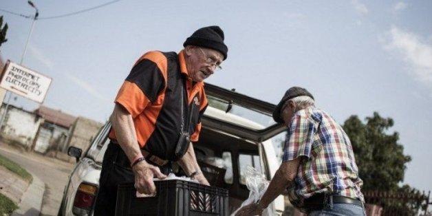 Adriaan Vlok (g), ancien ministre de l'apartheid, apporte de la nourriture au towsnhip d'Olievenhoutbosch, dans la banlieue de Pretoria, le 22 septembre 2015 en Afrique du Sud