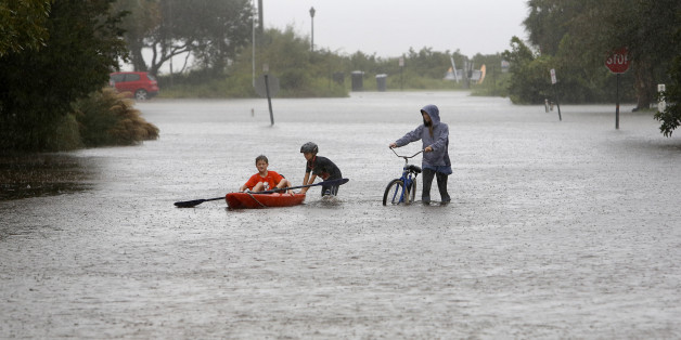 Joey Virgilio, 11, far left, sits in a kayak while his brother, Will, 9, wades in the water as mum, Kristen, pushes a bike during flood waters on Sullivan's Island, South Carolina, on Saturday