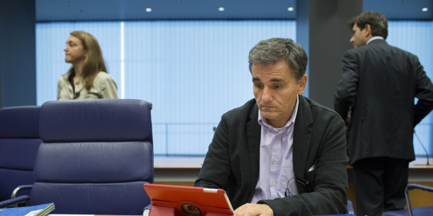 Euclid Tsakalotos, Greece's finance minister, looks at Apple Inc. iPad tablet device ahead of roundtable talks during a Eurogroup meeting in Luxembourg, on Monday, Oct. 5, 2015. French Finance Minister Michel Sapin said Greece needs to make good on its promises with euro-area lenders as soon as possible so the creditors can move on to discuss easing the country's debt burden. Photographer: Jasper Juinen/Bloomberg via Getty Images