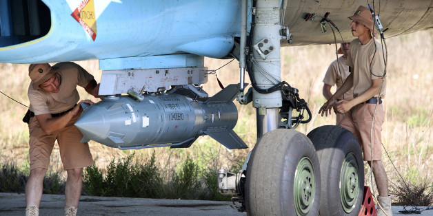 In this photo taken on Saturday, Oct.  3, 2015, Russian military support crew attach a satellite guided bomb to SU-34 jet fighter at Hmeimim airbase in Syria.  Russia has insisted that the airstrikes that began Wednesday are targeting the Islamic State group and al-Qaida's Syrian affiliates, but at least some of the strikes appear to have hit Western-backed rebel factions. (AP Photo/Alexander Kots, Komsomolskaya Pravda, Photo via AP)
