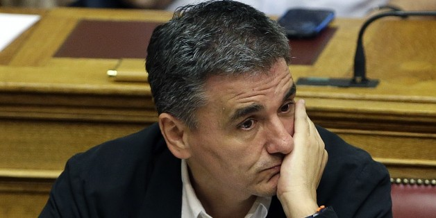 Greek Finance Minister Euclid Tsakalotos attends an emergency parliament session at the Greek Parliament in Athens, Wednesday, July 22, 2015. Greece's liquidity-starved banks got a new cash injection from the European Central Bank on Wednesday, hours before a key vote in parliament on further economic reforms demanded by international creditors in return for a third bailout.  (AP Photo/Thanassis Stavrakis)