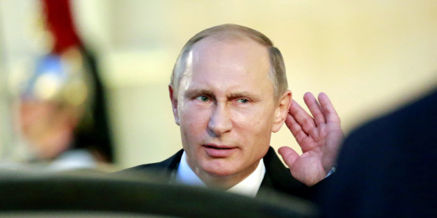 Russian President Vladimir Putin holds his hand on his ear while listening to a newsman's question as he leaves the Elysee Palace in Paris, France. Friday, Oct. 2 , 2015.  Russian President Vladimir Putin was in Paris with the leaders of Ukraine, France and Germany in a revived European push to bring peace to eastern Ukraine.The long-awaited summit in Paris on Friday is being overshadowed by international concerns about Russia's military intervention in Syria this week. (AP Photo/Jacqu