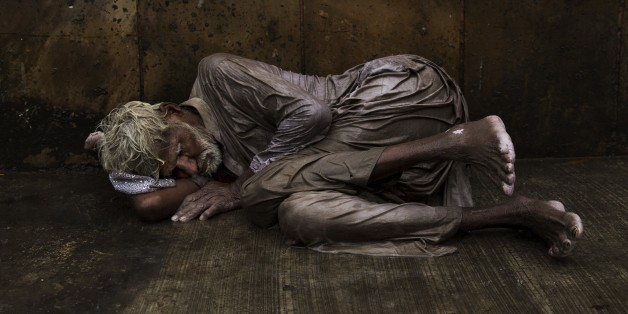 An Indian homeless man tries to sleep on a wet street during monsoon rains in New Delhi, India, Saturday, July 11, 2015. Tens of thousands of impoverished people live on the streets in New Delhi, where they struggle with constant hunger and extreme weather while sleeping nights next to busy intersections and roads. Some make camp in crowded alleyways, in abandoned lots or by garbage dumps. Many come from countryside villages in hopes of finding better economic opportunities in the Indian capital
