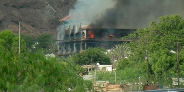 L'hôtel Al-Qasr, où logeait le Premier ministre yéménite, en feu après un attaque à la roquette, le 6 octobre 2015 à Aden