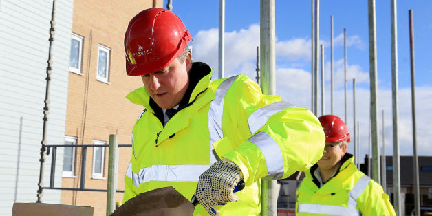Prime Minister David Cameron tries his hand at brick laying during a visit to the Barratt Homes Evolve development in Grays, Essex.
