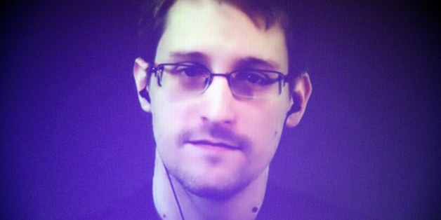 Former U.S. National Security Agency contractor Edward Snowden, who is in Moscow, is seen on a giant screen during a live video conference for an interview as part of Amnesty International's annual Write for Rights campaign at the Gaite Lyrique in Paris, France, Dec. 10, 2014. (AP Photo/Charles Platiau, Pool)