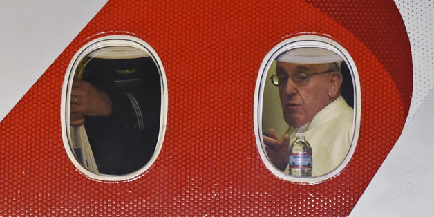 Pope Francis looks out the window a plane as he prepares to depart Philadelphia International Airport in Philadelphia, Sunday, Sept. 27, 2015, on his way back to Rome. Pope Francis wrapped up his 10-day trip to Cuba and the United States on Sunday. (AP Photo/Susan Walsh)