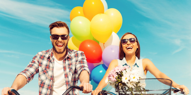 Low angle view of cheerful young couple smiling and riding on bicycles with colorful balloons in the background