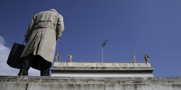 A pedestrian walks past statues, which stand at the top of the National Archaeological Museum of Greece as a Greek flag flies in central Athens, on Monday, March 16, 2015. Greece has slipped back into deficit so far this year, according to figures from the Bank of Greece. But the country's left-wing Prime Minister Alexis Tsipras ruled out any difficulties in making payments for public sector workers' salaries or state-backed pensions. (AP Photo/Petros Giannakouris)