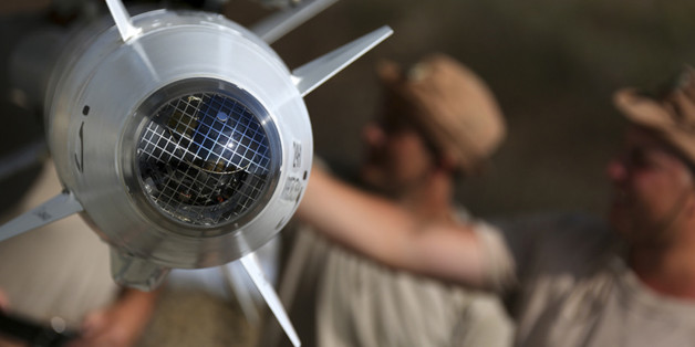 In this photo taken from Russian Defense Ministry official web site on Tuesday, Oct. 6, 2015,  Russian military support crew inspect missiles attached to their jet at an air base in Syria. at an air base Hmeimim in Syria. A spokeswoman for the Russian foreign ministry has rejected claims that Russia in its airstrikes in Syria is targeting civilians or opposition forces. (Russian Defense Ministry Press Service via AP)