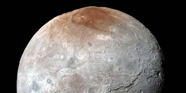 This image released by NASA on Thursday, Oct. 1, 2015, shows Charon, in enhanced color captured by NASA's New Horizons spacecraft just before closest approach on July 14, 2015. Massive canyons and fractures are clearly visible on Charon, which is more than half of Pluto's size. (NASA/JHUAPL/SwRI via AP)