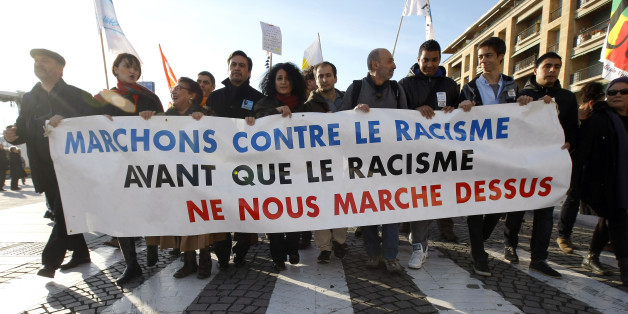 """People demonstrate during a march against the racism,  in Marseille , southern France, Saturday, Nov. 30, 2013. Banner reads """"Let us walk against the racism before the racism walks on us"""". (AP Photo/Claude Paris)"""