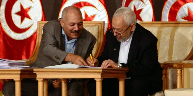In this photo taken Saturday, Oct. 5, 2013, Tunisia's ruling Islamist Ennahda party leader Rached El Ghannouchi, right, signs documents during a meeting as part of the dialogue between Tunisia's ruling Islamists and the opposition at the Palais des Congres, in Tunis. Nearly all of Tunisia's feuding political parties on Saturday signed on to a roadmap designed to break their months-old impasse and put an end to the country's drawn-out democratic transition. (AP Photo/ Hassene Dridi)