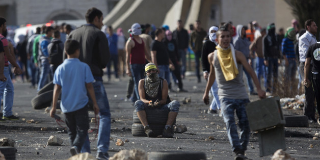 A Palestinian protester sits on tires during clashes with Israeli troops near Ramallah, West Bank, Thursday, Oct. 8, 2015. Dozens of Palestinian protesters threw stones at Israeli troops near the West Bank city of Ramallah and elsewhere on Thursday. Israeli forces responded with tear gas and stun grenades. (AP Photo/Majdi Mohammed)