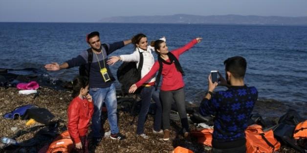 Des réfugiés pausent pour les photographes à leur arrivée sur l'île de Lesbos, le 9 octobre 2015