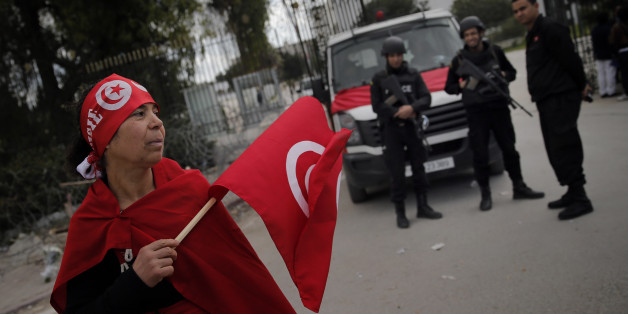 A woman holds a Tunisian flag as policemen stand guard at the National Bardo Museum two days after gunmen attacked the museum and killed scores of people in Tunis, Tunisia, Friday, March 20, 2015. The Islamic State group issued a statement Thursday claiming responsibility for the deadly attack on Tunisia's national museum that killed scores of people, mostly tourists. (AP Photo/Christophe Ena)