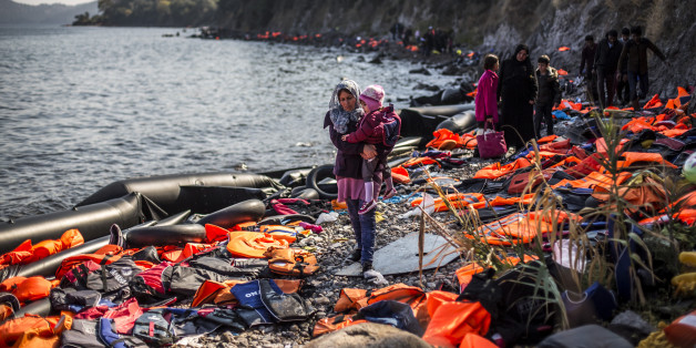 SKALA SIKAMINIAS, GREECE - OCTOBER 04:  A woman carries her child as she arrives with other refugees on the shores of the Greek island of Lesbos after crossing the Aegean sea from Turkey on an inflatable boat on October 4, 2015 near village of Skala Sikaminias, Greece. Despite bad weather due to the upcoming Autumn, migrants and refugees are risking their lives in search of a better one in the European Union. Officals have warned that a rise in migrant deaths is expected as weather conditions gradually worsen.  (Photo by Matej Divizna/Getty Images)
