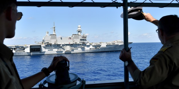 The commander (R) Stefan Klatt  of German navy frigate ship Werra salutes the Italian navy carrier Cavour as it sails in the Mediterranean Sea, not far from Libyan territorial waters, on September 23, 2015. The German ship is part of the EU operation EuNavFor Med, rescuing migrants crossing the Mediterranean Sea from North Africa to Europe. AFP PHOTO / ALBERTO PIZZOLI        (Photo credit should read ALBERTO PIZZOLI/AFP/Getty Images)