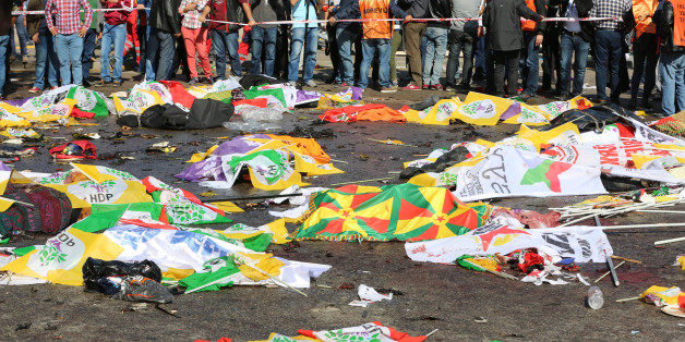 Bodies of victims are covered with flags and banners at the site of an explosion in Ankara, Turkey, Saturday, Oct. 10, 2015. Turkey's health minister says two bomb explosions in the Turkish capital have killed scores of people. The explosions occurred minutes apart near Ankara's main train station as people were gathering for a rally, organized by the country's public sector workers' trade union and other civic society groups. The rally aimed to call for an end to the renewed violence between Ku
