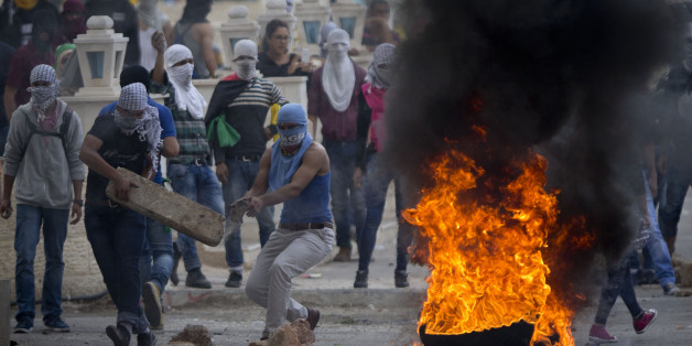 Palestinians improvise a barricade during clashes with Israeli troops near Ramallah, West Bank, Saturday, Oct. 10, 2015. Palestinians carried out two stabbing attacks in Jerusalem on Saturday before being shot dead by police, while another two Palestinians were killed during a violent demonstration near the Gaza border fence, the latest in a series of stabbing attacks against civilians and soldiers that have spread across Israel and the West Bank in the past week. The violence, including the fir