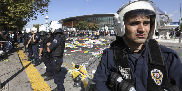 Turkish police officers secure the area at the site of an explosion, where the bodies of victims were covered with flags and banners,  in Ankara, Turkey, Saturday, Oct. 10, 2015. The two bomb explosions targeting a peace rally in the capital Ankara has killed dozens of people and injured scores of others. The explosions occurred minutes apart near Ankara's main train station as people were gathering for the rally, organized by the country's public sector workers' trade union and other civic soci