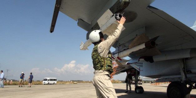 In this photo taken on Monday, Oct. 5, 2015, a Russian pilot fixes an air-to-air missile at his Su-30 jet fighter before a take off at Hmeimim airbase in Syria. NATO also strongly criticized the Russian air campaign in Syria that began Wednesday. (AP Photo/Dmitry Steshin, Komsomolskaya Pravda, Photo via AP)