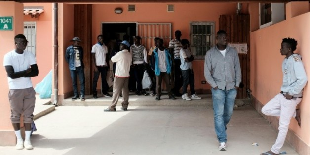 Des migrants attendent devant un centre d'accueil pour les demandeurs d'asile à Mineo, en Sicile, le 21 avril 2015