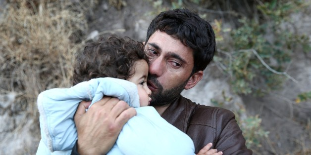 LESBOS, GREECE - OCTOBER 12:  A refugee man kisses his child as they arrive by a rubber boat on the Greek island of Lesbos after crossing the Aegean sea on October 12, 2015. Refugees who begin a journey with a hope to have high living standards away from conflicts, use Greece's Lesbos Island as a transit point on their way to Europe. (Photo by Ayhan Mehmet/Anadolu Agency/Getty Images)