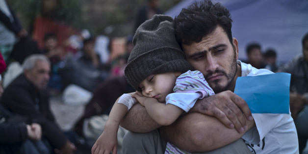 A Syrian refugee child sleeps on his father's arms while waiting at a resting point to board a bus